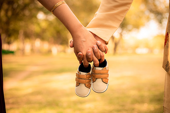 Mann und Frau halten in ihren Händen gemeinsam Kinderschuhe